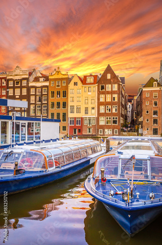 Photo Stands Amsterdam Traditional old buildings and boats at sunset in Amsterdam, Netherlands.