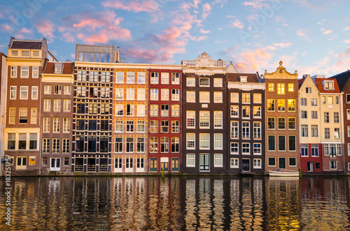 Photo  Traditional old buildings and boats at sunset in Amsterdam, Netherlands