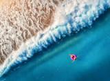 Widok z lotu ptaka młodej kobiety dopłynięcie na różowym pływanie pierścionku - 183253907