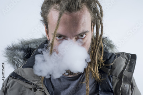 Man dreadlocks smoking electronic cigarette . Wallpaper Mural