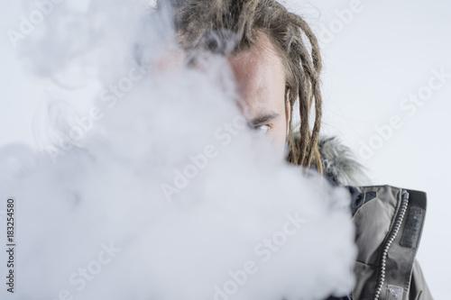 Fotografie, Obraz  Man dreadlocks smoking electronic cigarette .
