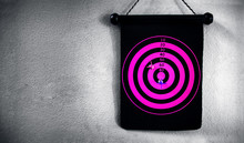 Circular Pink Target With Magnetic Darts On The Wall.