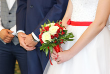 Wedding Bouquet In Hands Of Bride. The Bride And Groom In The Registry Office