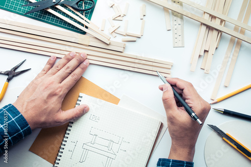 Male working on worktable with balsa wood material Wallpaper Mural