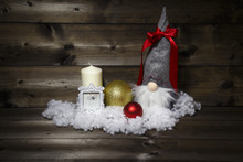 Christmas Decoration With White Candle, Picture Frame, Shiny Christmas Balls, Snow And Scandinavian Traditional Gnome Tomte, Nisse, Tomtenisse, Tonttu With A Red Ribbon On A Wooden Background