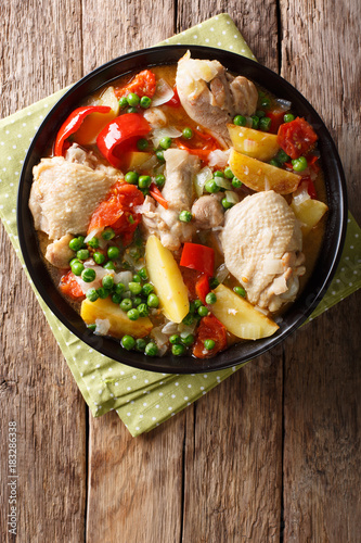 Chicken meat stewed with vegetables and spices close-up in a bowl. Vertical top view