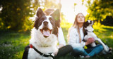 Fototapeta Zwierzęta - Romantic happy couple in love enjoying their time with pets in nature
