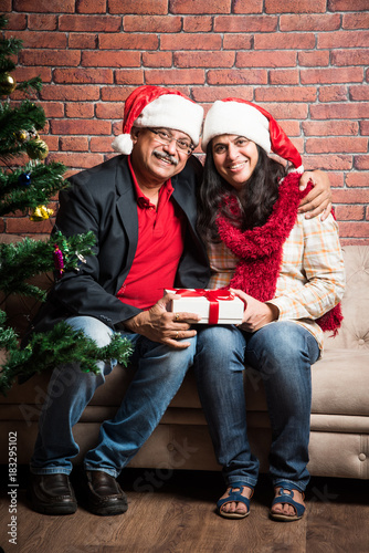 middle aged indian smart couple celebrating christmas and exchanging gifts while sitting on sofa