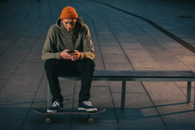 Skateboarder Sitting On Bench ...