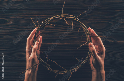 Tela cropped image of woman holding crown of thorns in hands