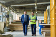 canvas print picture - Full length portrait of young workman giving tour of modern factory to handsome mature businessman discussing possible investment, copy space
