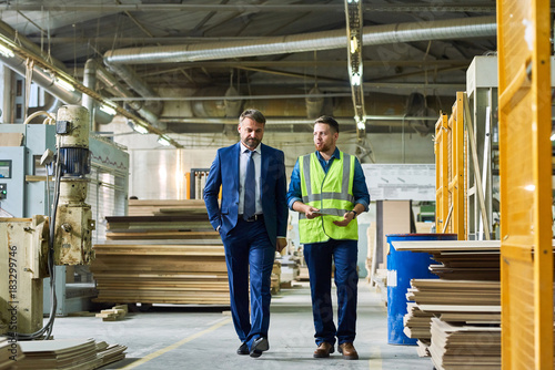 Full length portrait of young workman giving tour of modern factory to handsome Wallpaper Mural