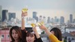 Outdoor shot of young people toasting drinks at a rooftop party. Young asian girl friends hanging out with drinks. Holiday celebration festive party. Teenage lifestyle party. Freedom and fun outdoor.