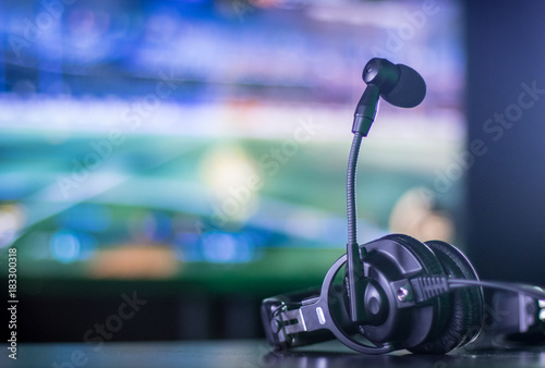 Photographie Headset resting on table with screen in background