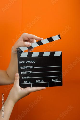 Photo  movie clapper on orange background, cinema concept
