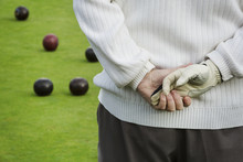 Rear View, A Man Standing With His Hands Clasped Behind Him, One Hand In A Playing Glove, At A Lawn Bowls Match,