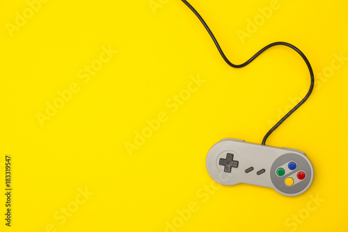Retro computer gaming controller on a bright yellow background Tablou Canvas