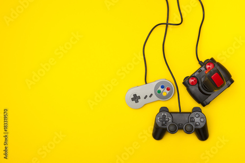 Retro computer gaming controllers on a bright yellow background Tablou Canvas