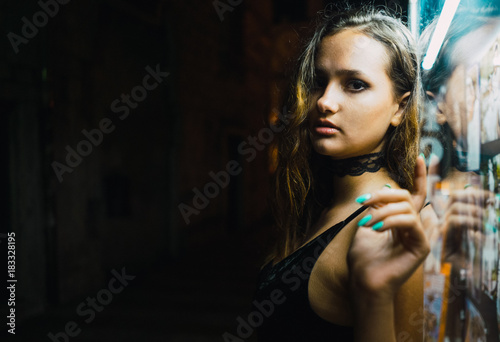 Woman leaning against window on dark street