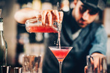 barman preparing and pouring red cocktail in martini class. cosmopolitan cocktail with bar background
