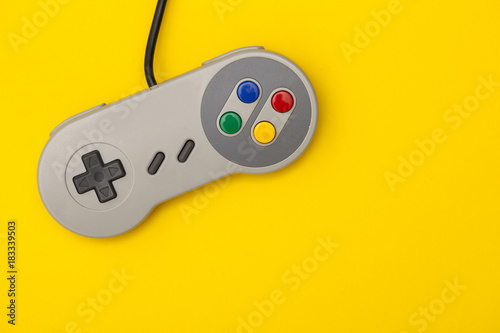 Retro computer gaming controller on a bright yellow background Poster Mural XXL