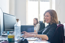 Women In Startup Business And Entrepreneurship. Yound Devoted Female AI Programmers And IT Software Developers Team Programming On Desktop Computer In Startup Company Share Office Space.
