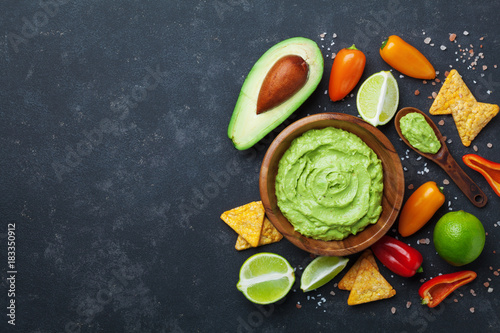 Traditional mexican food. Bowl guacamole sauce with avocado, lime and nachos on black table top view. Copy space for recipe.