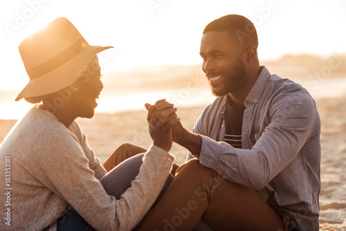Fotografia  Young African couple sitting together on a beach at sunset