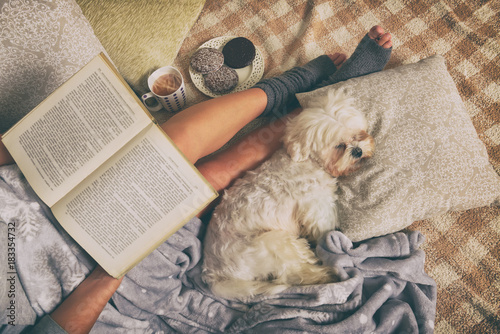 Photo Woman lying on bed with dog