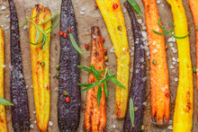 Baked Carrots On A Baking Sheet With Rosemary, Coarse Sea Salt And Pepper. Colorful Vegetables And Spices. Vegetarian Dish