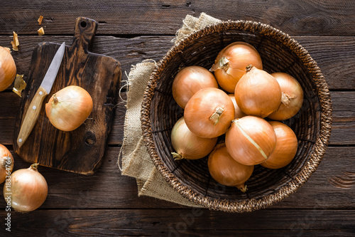 Fotografie, Obraz Fresh onion in basket on wooden table, top view