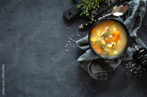 Fresh fish soup in bowl on dark background, top view