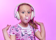 canvas print picture - little girl with headphones blowing up a bubble of gum on a pink background