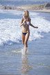 Young blonde woman enjoying the perfect weather on the beach.