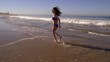 Attractive woman running on the beach. Slow Motion.