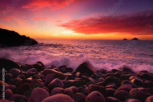 Foto op Plexiglas Crimson Purple tinted waves breaking on a rocky beach at sunset over Porth Nanven in the Cot Valley of Cornwall, England
