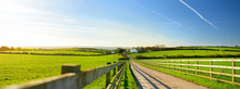 Fence Casting Shadows On A Road Leading To Small House Between Scenic Cornish Fields Under Blue Sky, Cornwall, England