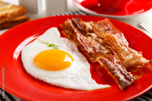 Foto op Plexiglas Gebakken Eieren Plate with fried egg and bacon, closeup