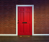 Bright red front door and welcome mat with wood porch floor.