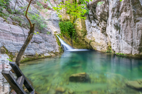 A small picturesque waterfall in a cozy mountain lagoon.