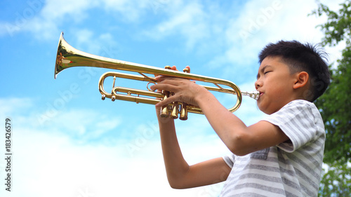 Carta da parati Asian boy playing trumpet with blue sky background.