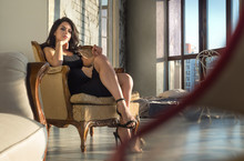 Elegant Beautiful Woman In A Black Cocktail Dress And High Heels Sitting In A Contemporary Armchair In The Sunset Light