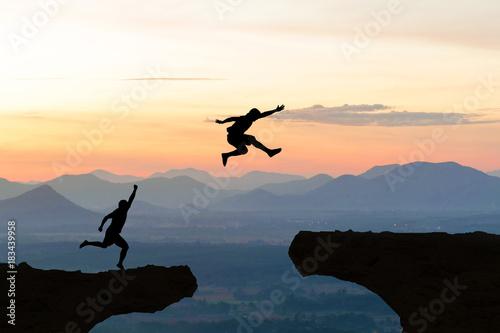 Fotografia Men jump cliff sun light over silhouette