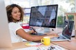 Female executive working over graphic tablet at her desk in