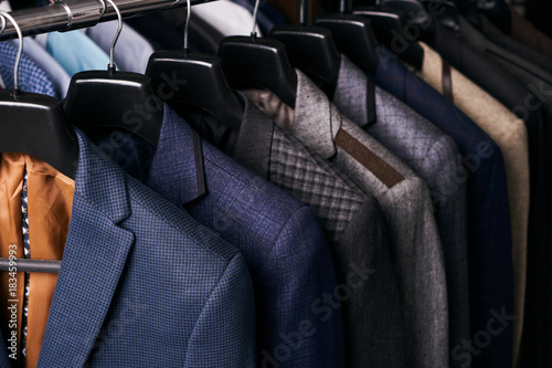 Mens suits on hangers in different colors Fototapeta