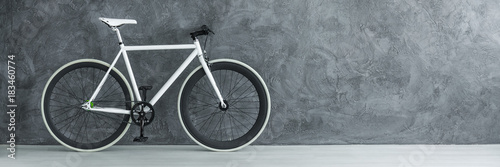 White bicycle against concrete wall Canvas Print