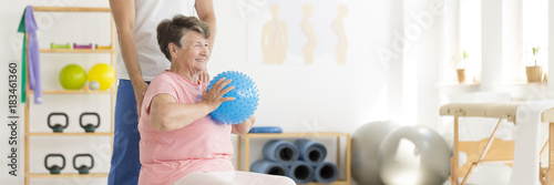 Elderly woman exercising with ball