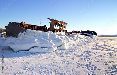 Keuken foto achterwand Schip The abandoned old rusty ship placing on the coast of frozen lake. Baikal, Russia