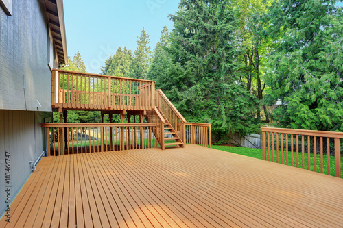 Fototapeta Backyard view of grey rambler house with upper and lower decks obraz