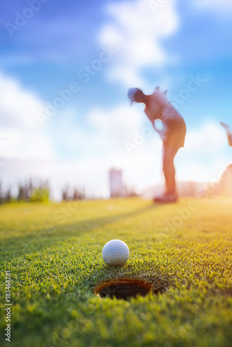 Poster Golf Golf ball putting by woman golf player in background, golf ball spining to the hold on the green of golf course with early light of sunset